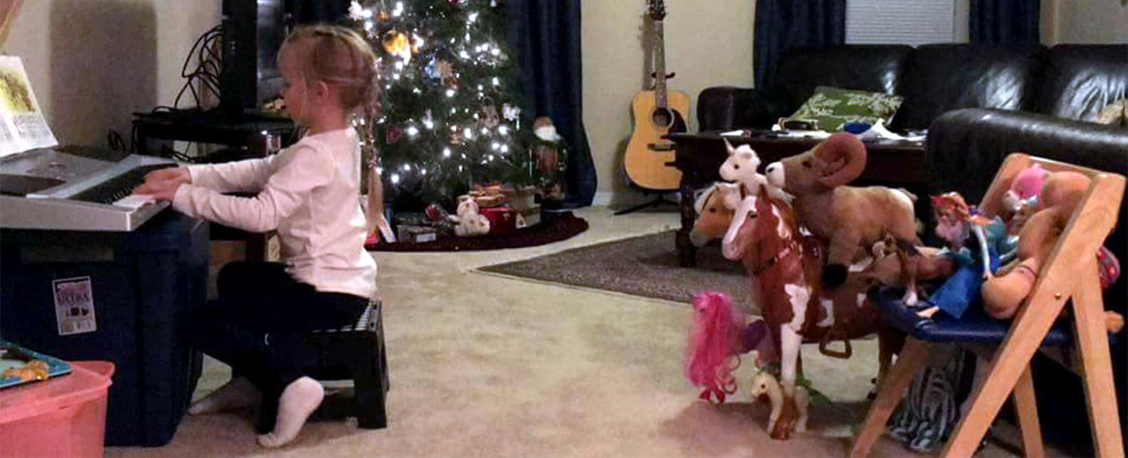 Music student practicing for her first recital with her stuffed animal audience.